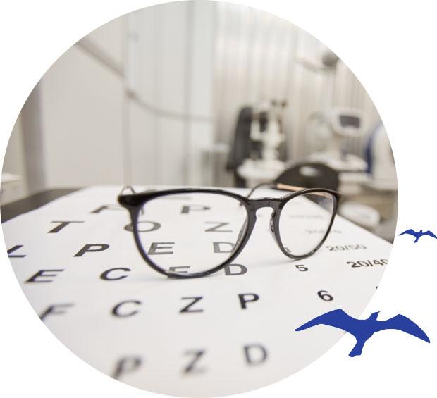 Óculos apoiado em uma folha com letras em um consultório oftalmológico. Símbolo da gaivota está presente na lateral direita.
