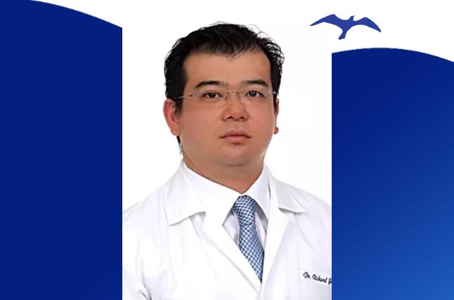 Doutor Richard Hida com símbolo da gaivota ao fundo.